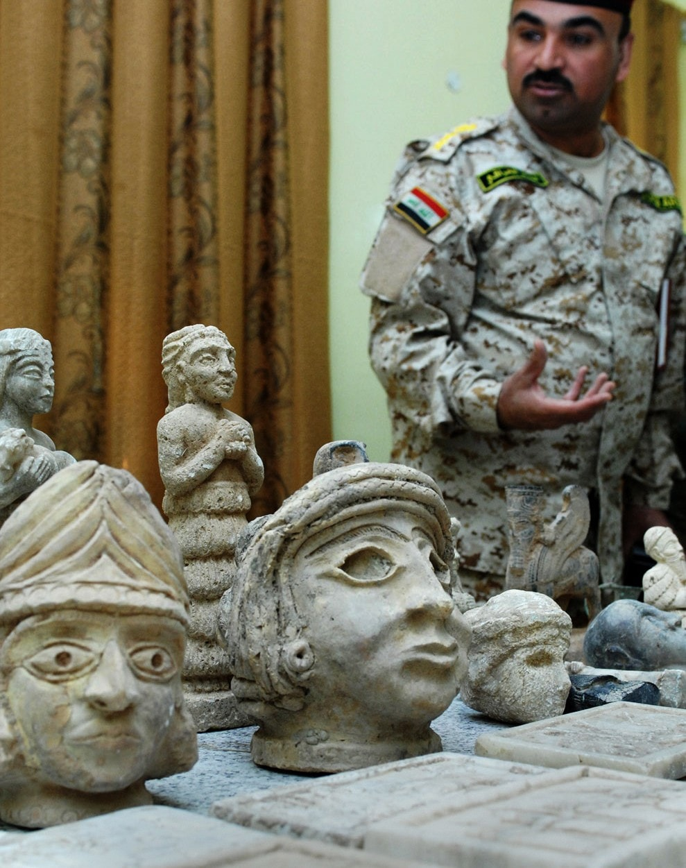 Iraqi colonel ali sabah standing next to artefacts - stone heads - retrieved after the looting