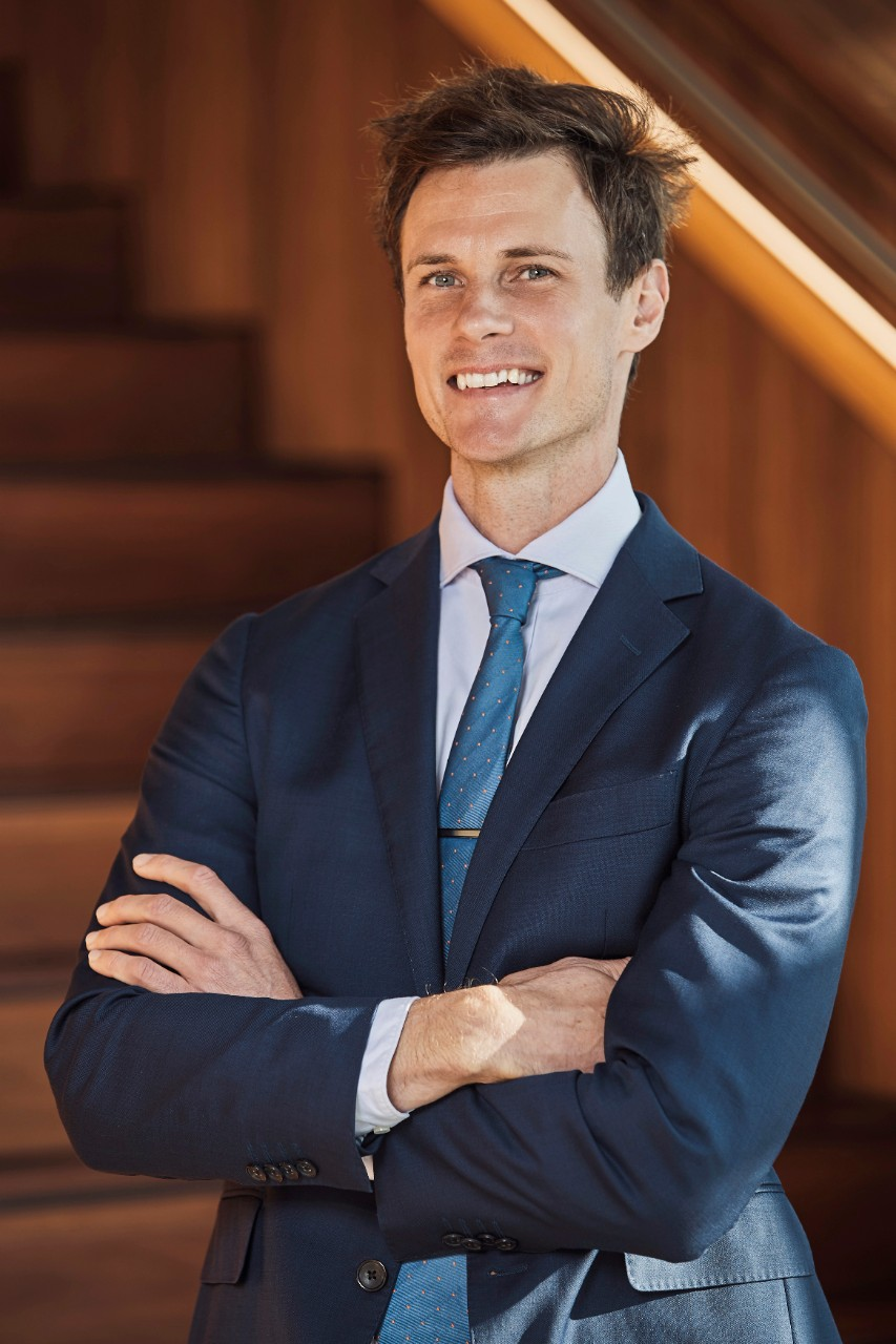 Dr Nick Fuller, arms crossed, standing in front of stairs