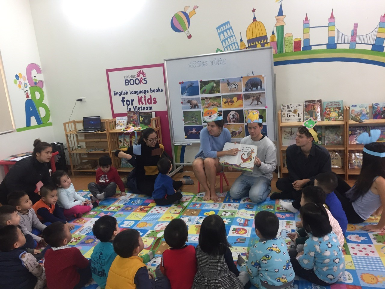 University of Sydney students (L-R) Louisa, Mike, Max and Natasha, leading story time with Vietnamese children at the Kids Needs Books social enterprise in Hanoi.