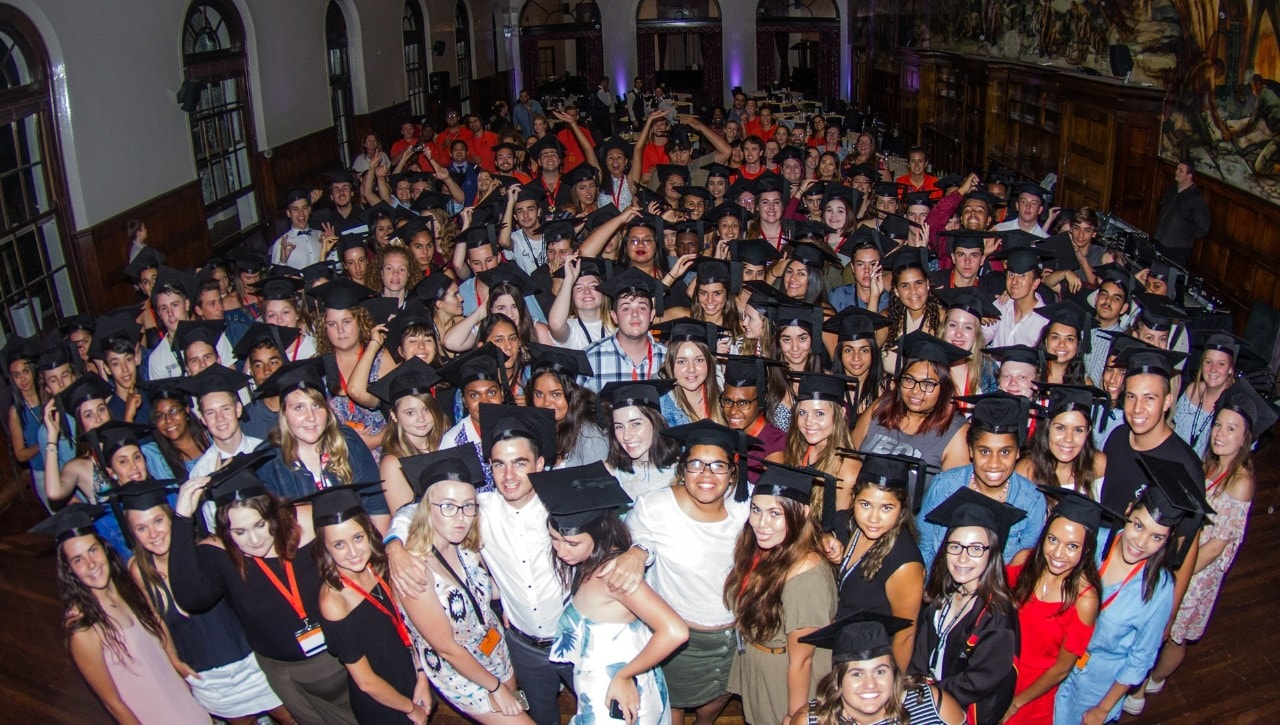 A photo of a large group of young people wearing academic caps.