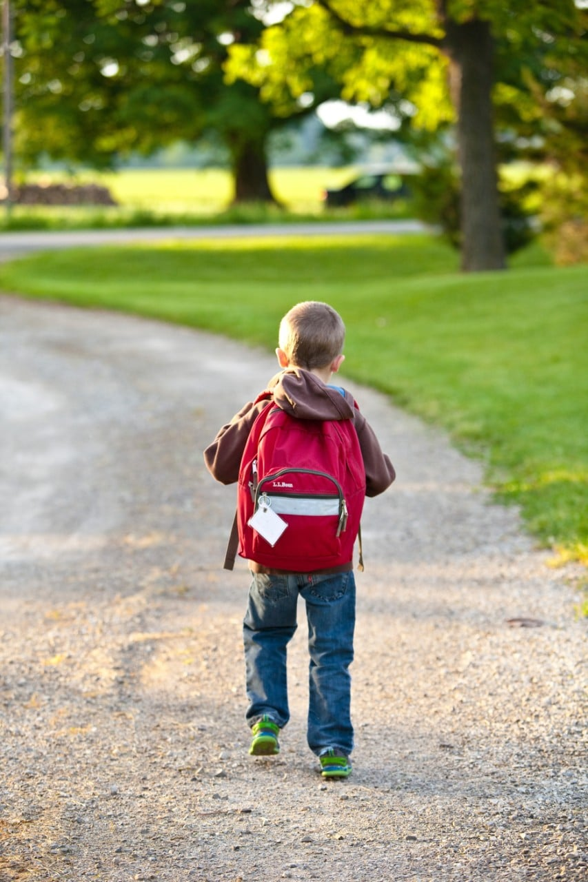 Child carrying large backpack