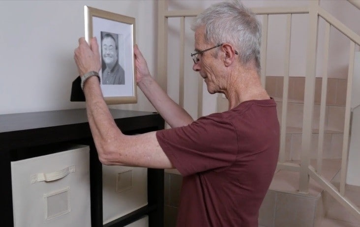 Older man looks at photo of friend who has passed away