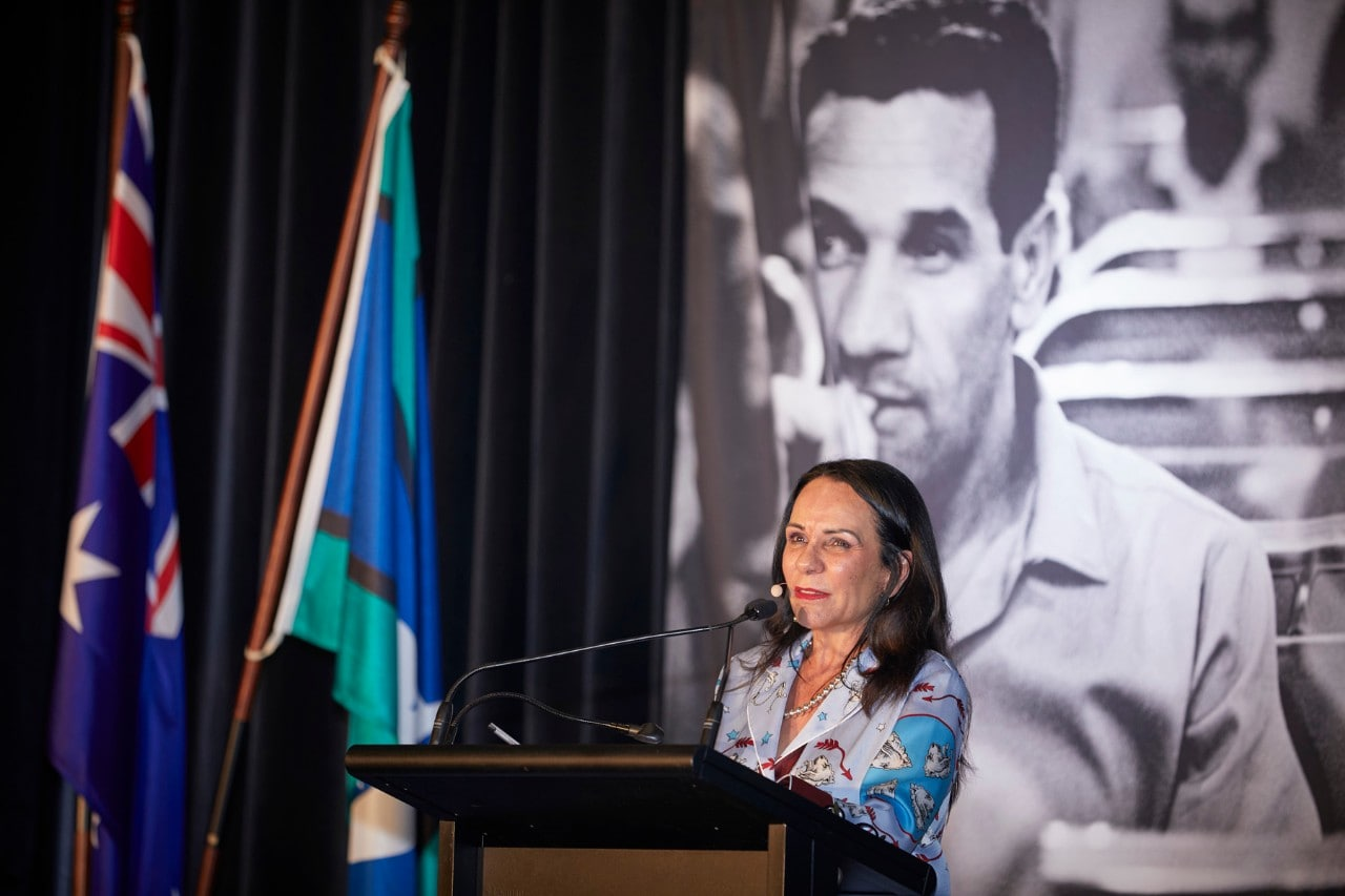 Linda Burney MP standing at a lecturn with a poster of Charles Perkins behind