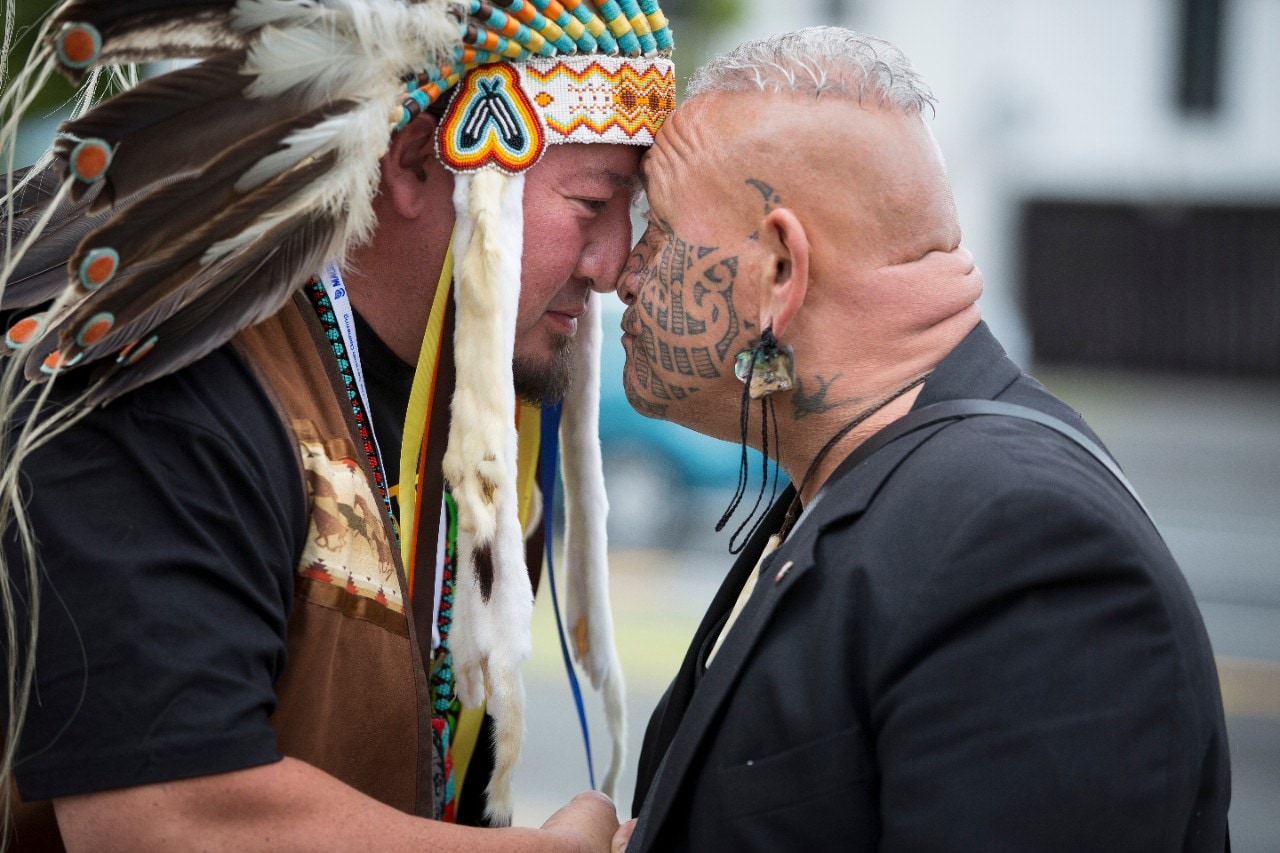 Two men, one wearing a traditional headdress, embracing