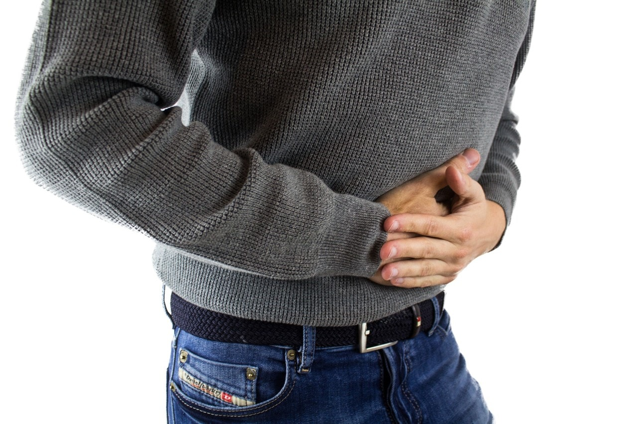 photo of a man holding his stomach in pain