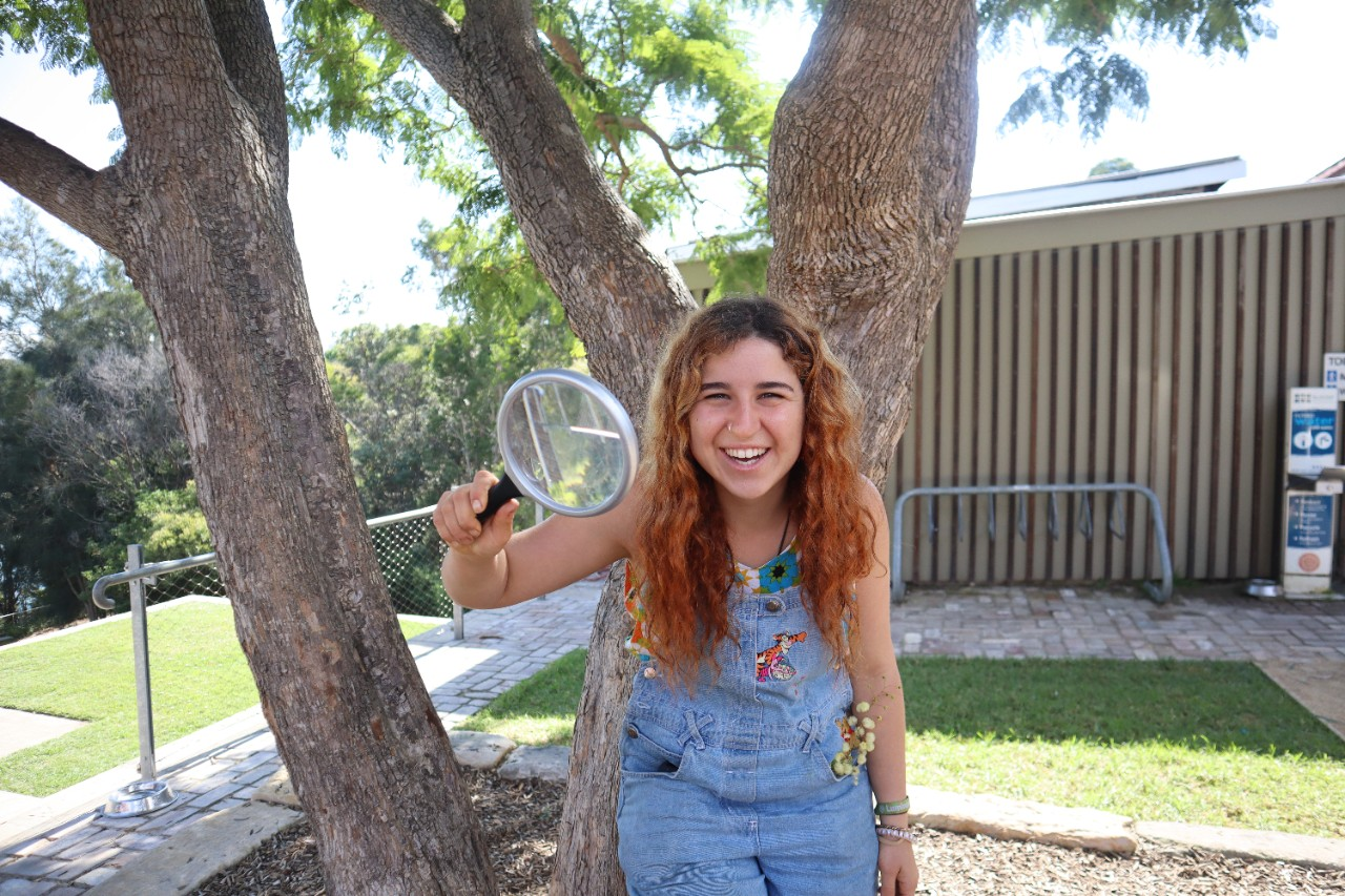 Photo of PhD student Amelie Vanderstock holding a magnifying glass