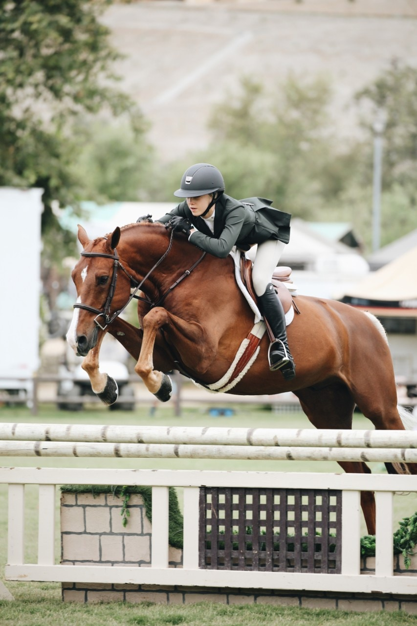 photo of a woman riding a horse in an equestrian event