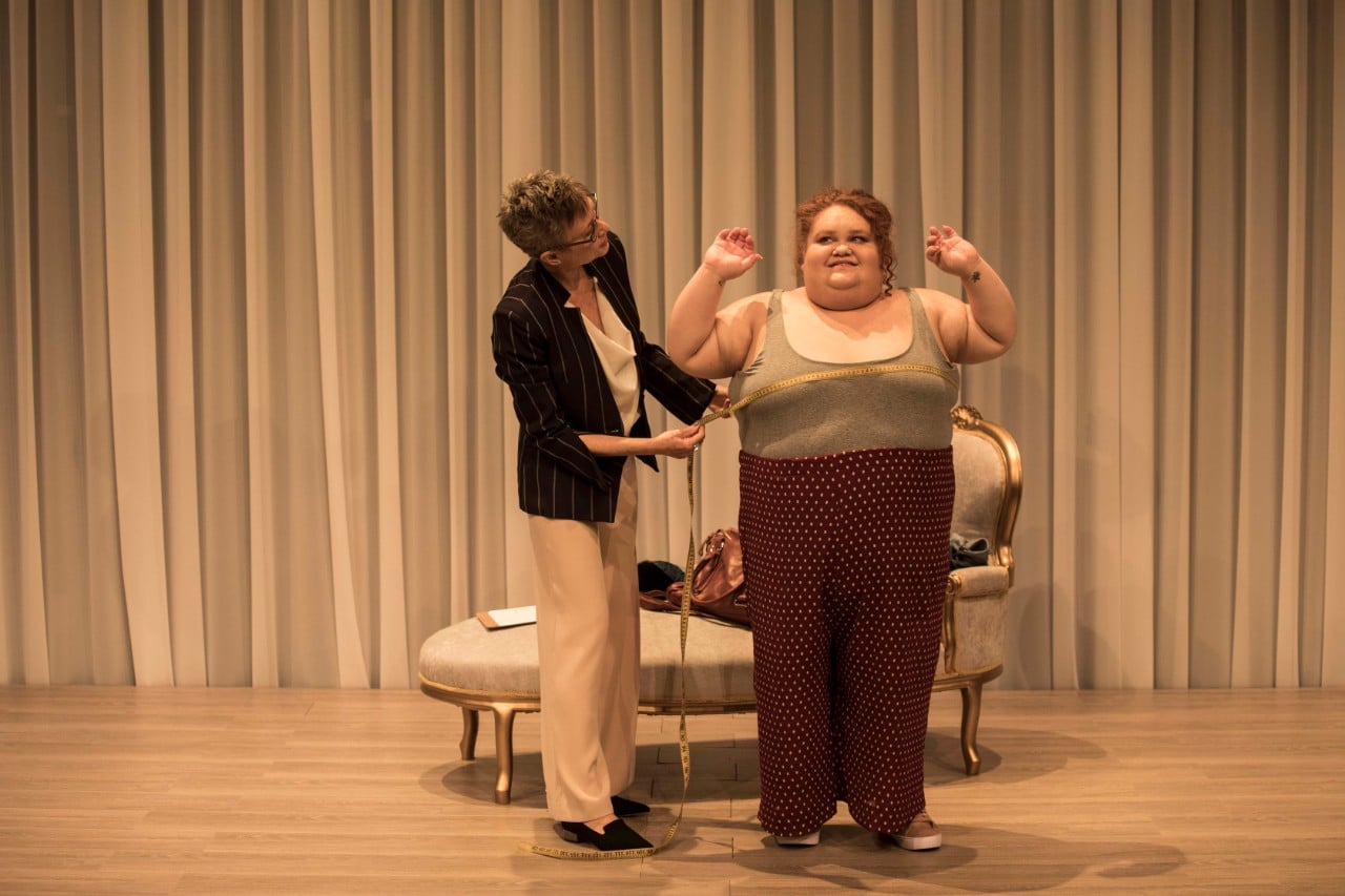photo of actor Megan Wilding, a larger woman, being measured for a wedding dress