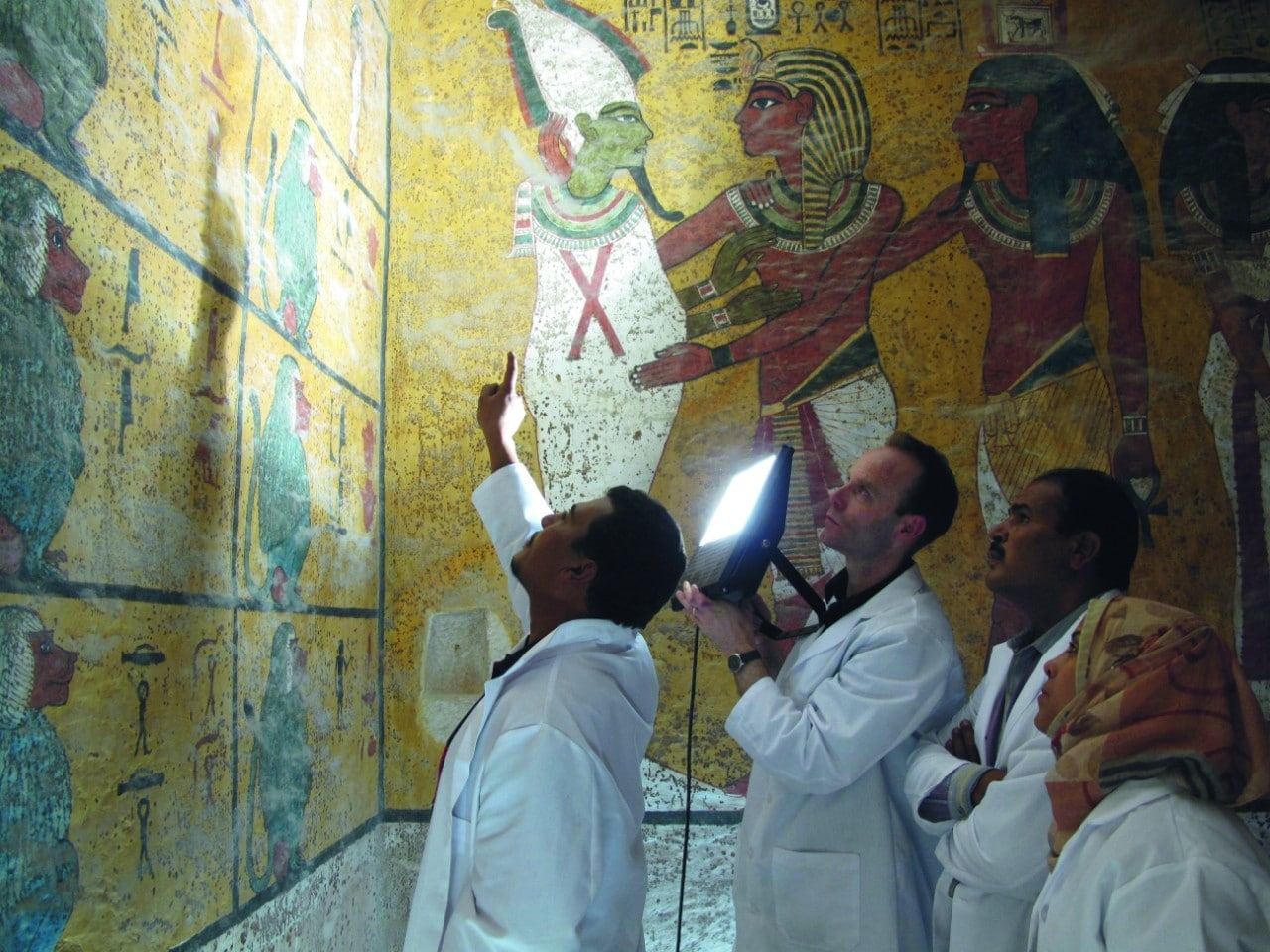 Four people in white lab coats - one pointing a large light at the wall - are looking at decoratively painted walls in the tomb of Tutankhamen.