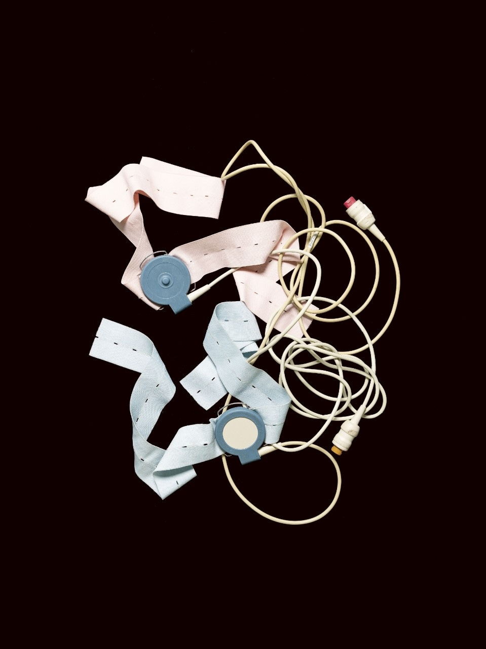 A tangle of blue and pink straps and wires. The outmoded cardiotocography monitor (known as a CTG), on a black background.