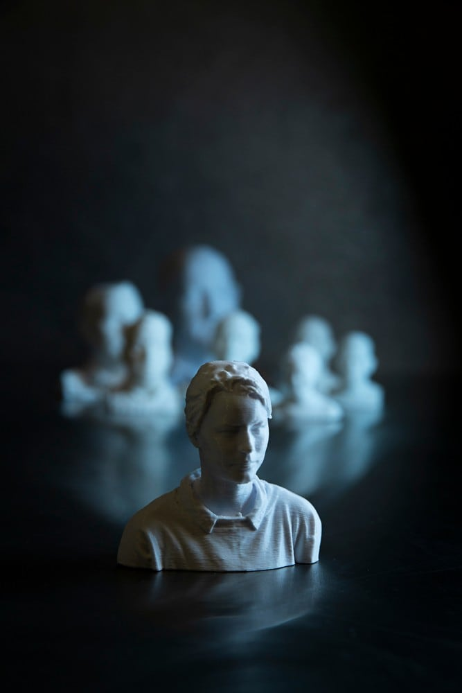 Sitting on a polished table is a 3D printed, head and shoulders rendering of Cheng. It is like white marble, and she is wearing a collared shirt. Behind her is a crowd of 3D models of Cheng's workmates, though they are blurry and indistinct. The image has a darkness about it but side lit in tones of blue.
