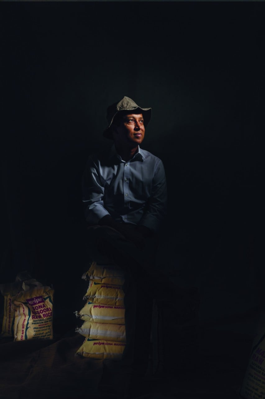 Shaymal Chowdury wearing a cap and in a darkened space with his face and other touch points gently illuminated. He is sitting on sacks of rice.