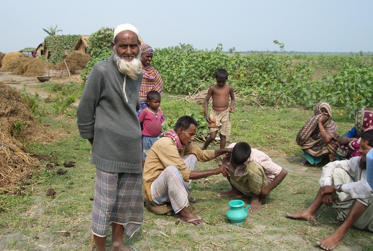 Under a clear, blue sky, several members of a rural Bangladeshi family are gathered. Standing in the foreground is a white-bearded elder looking at the camera.