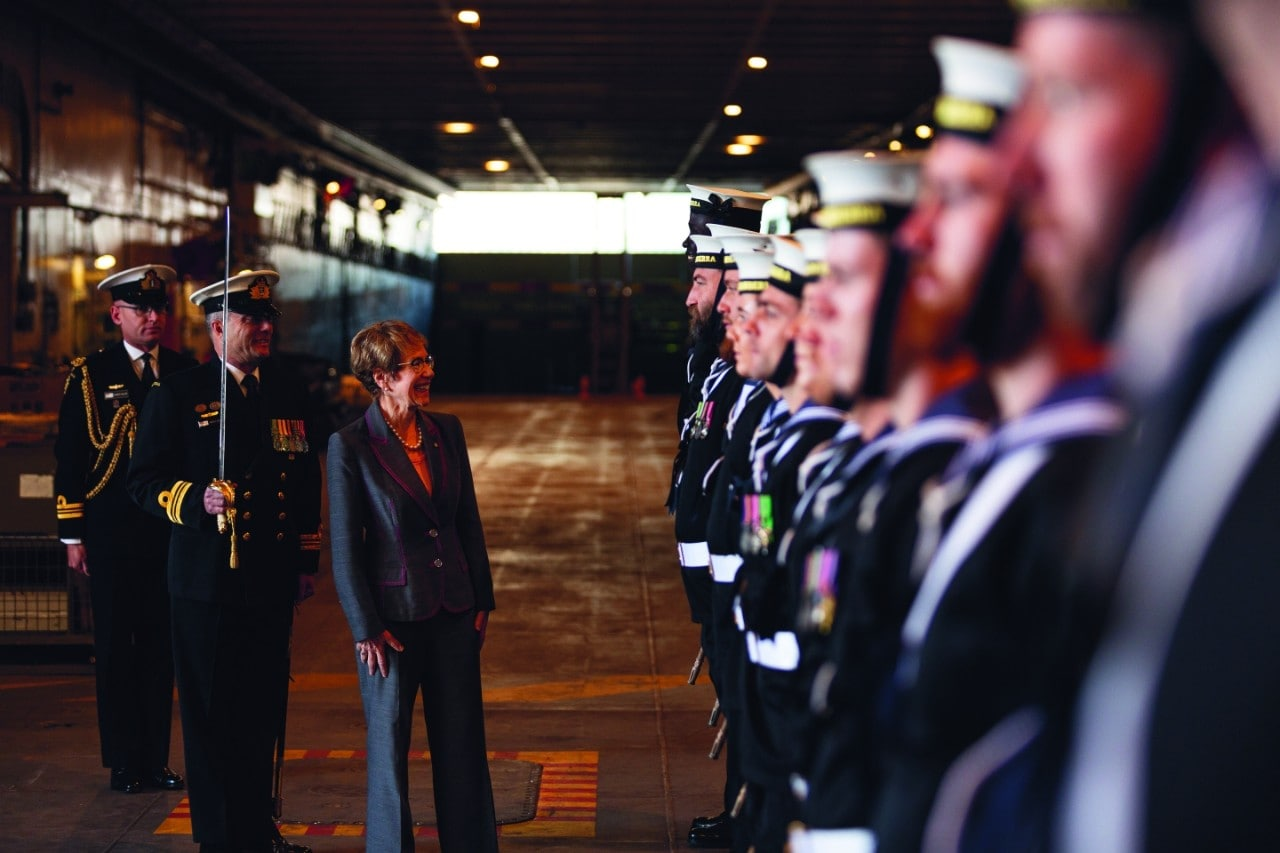 On the below deck of a navy ship and in low light, Beazley is inspecting a squad of sailors. She is on the left of frame with two officers dressed in ceremonial uniforms, one holding a sword. She is looking at a row of sailors on the right, with the closest to the camera blurring into the frame.
