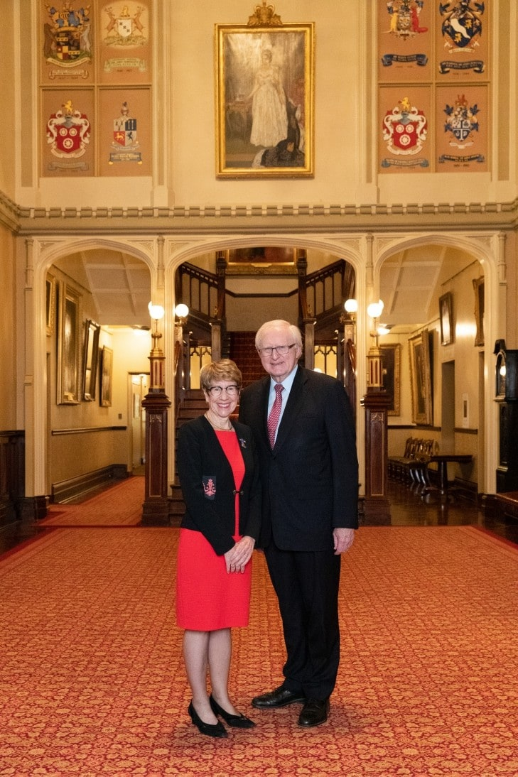 Margaret Beazley and Dennis Wilson posed standing together in the formal entrance foyer of NSW Government House. Behind them is a grand staircase and there is a sense of height and space. The carpet is red, and the walls seem golden being adorned with two crest banners and an old portrait in the centre.