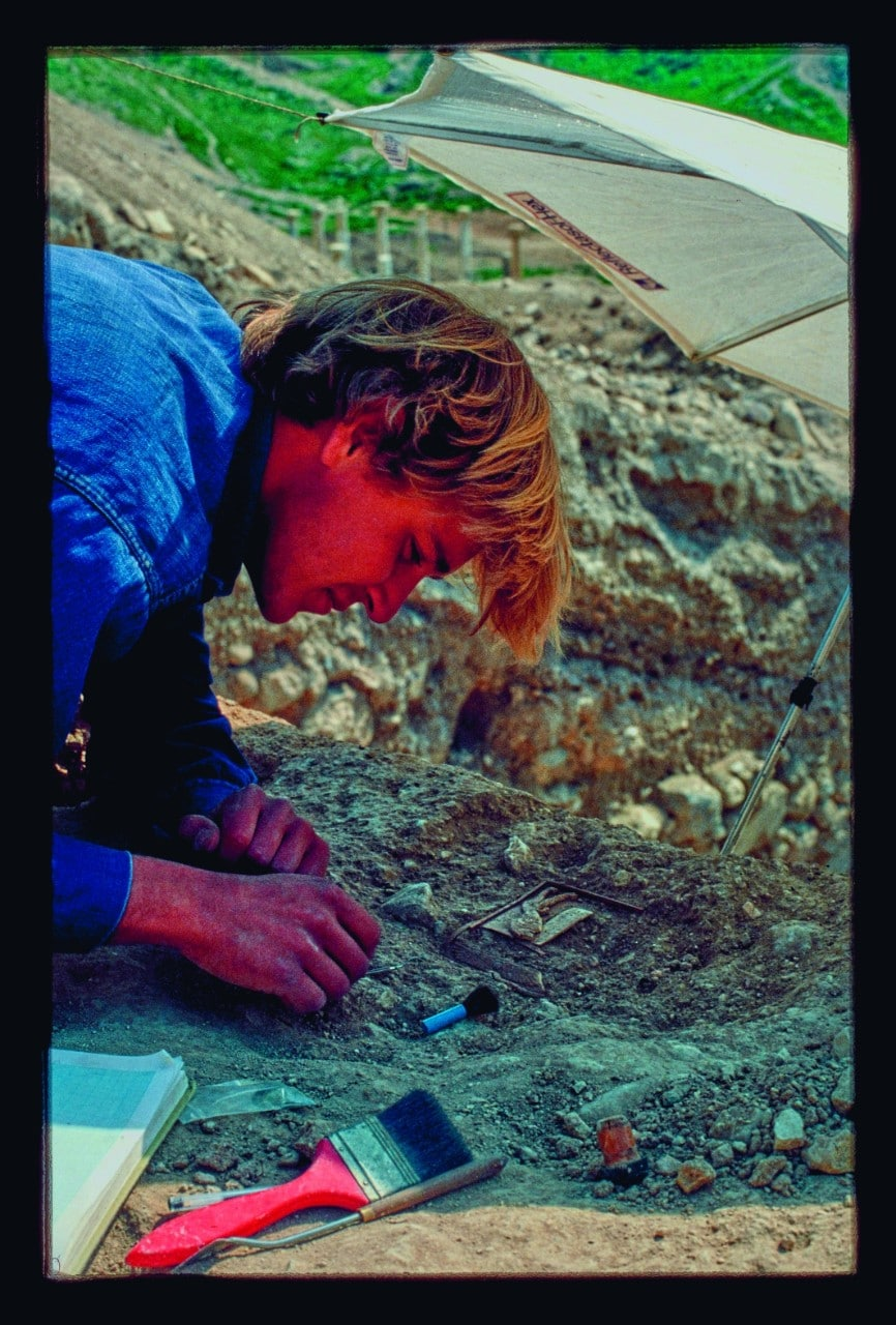 A young Tim Potts in Pella, Jordan, blonde hair tumbling forward, he is hunched over a small object - the lion box - which he is carefully removing from the grey earth and rubble that is holding it. Beside him is a large bright red paint brush, that he has been using to sweep dirt away.
