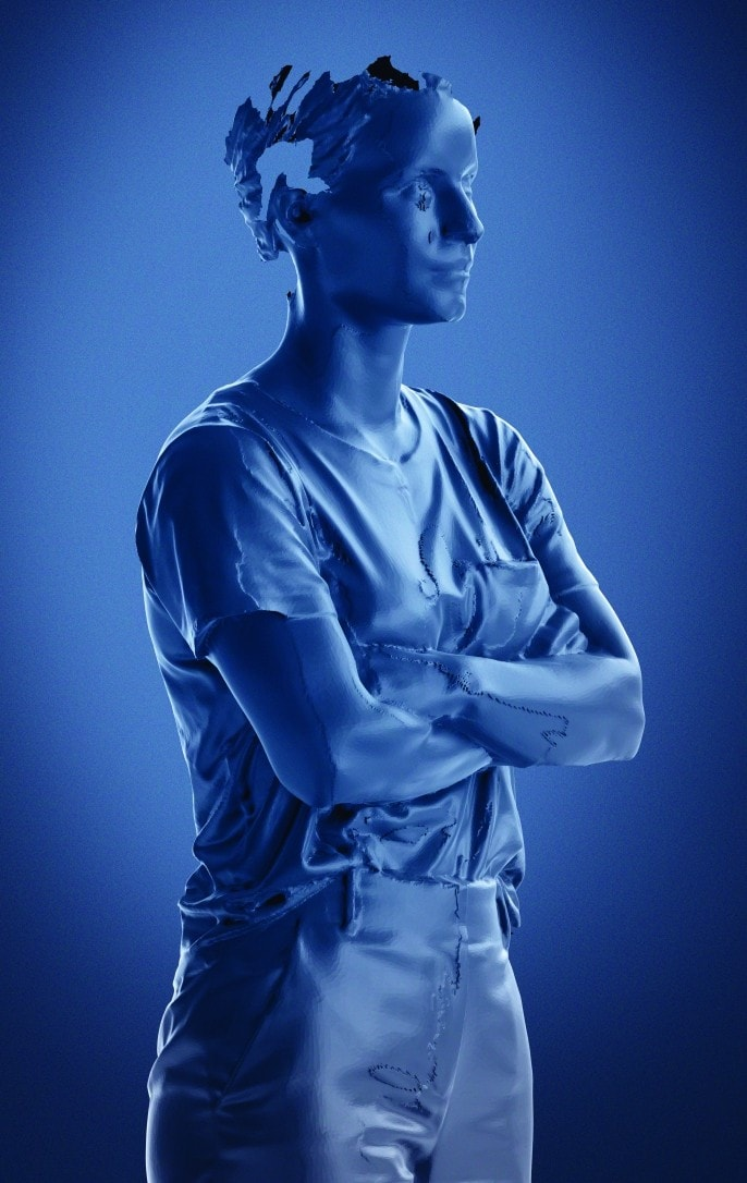 A partial, sci-fi looking computer-generated image of Cheng with folded arms. The images is made up of vivid tones of blue.