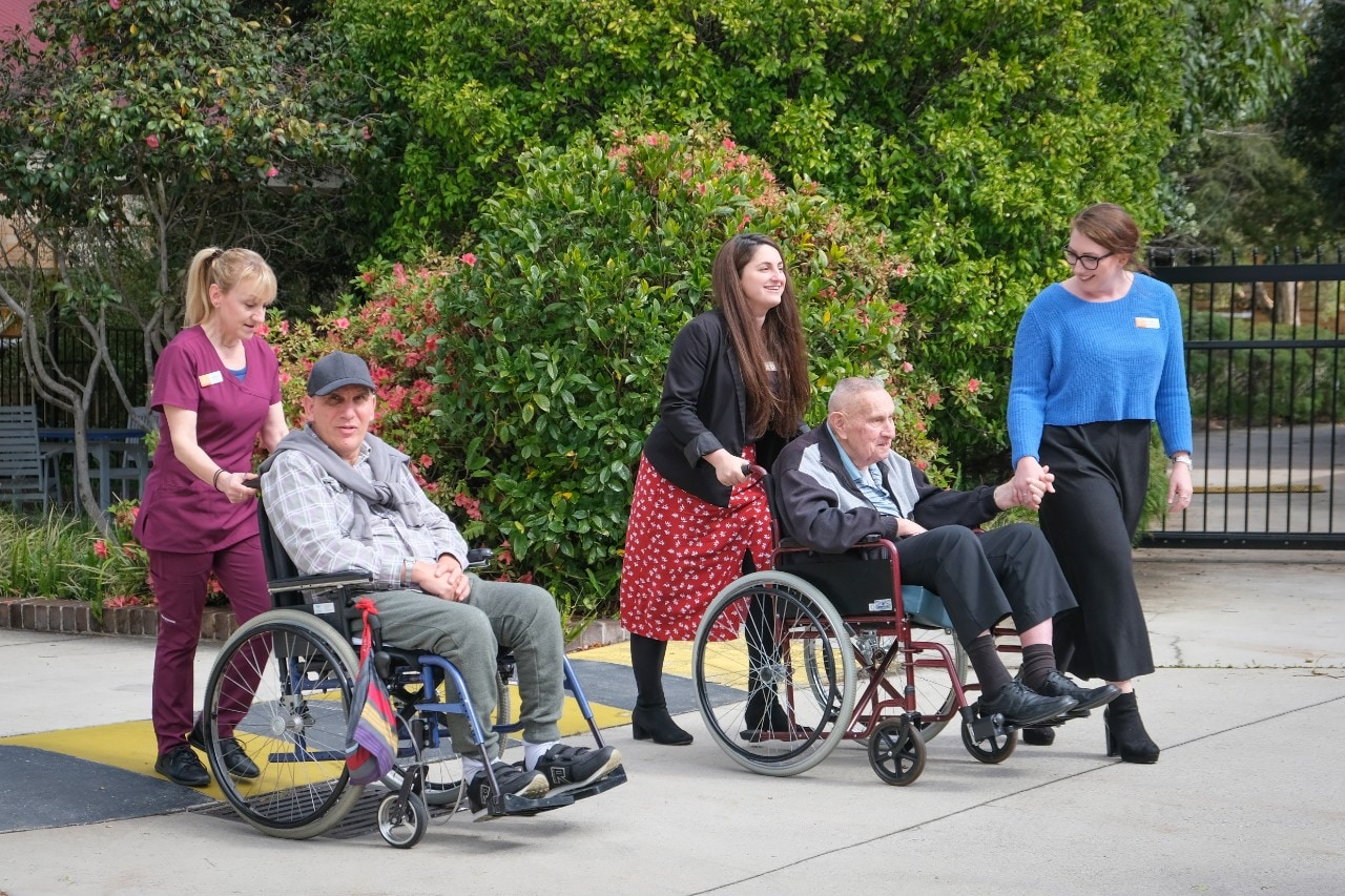 Students and residents in wheelchairs or walking up hill
