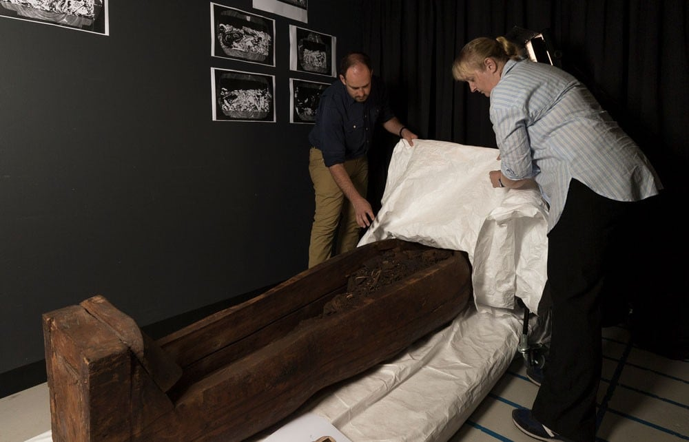 Fraser and Lord peel back a sheet to reveal the wooden mummy coffin