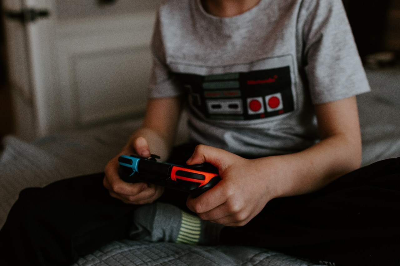 Photo of a kid with his hands on a game controller