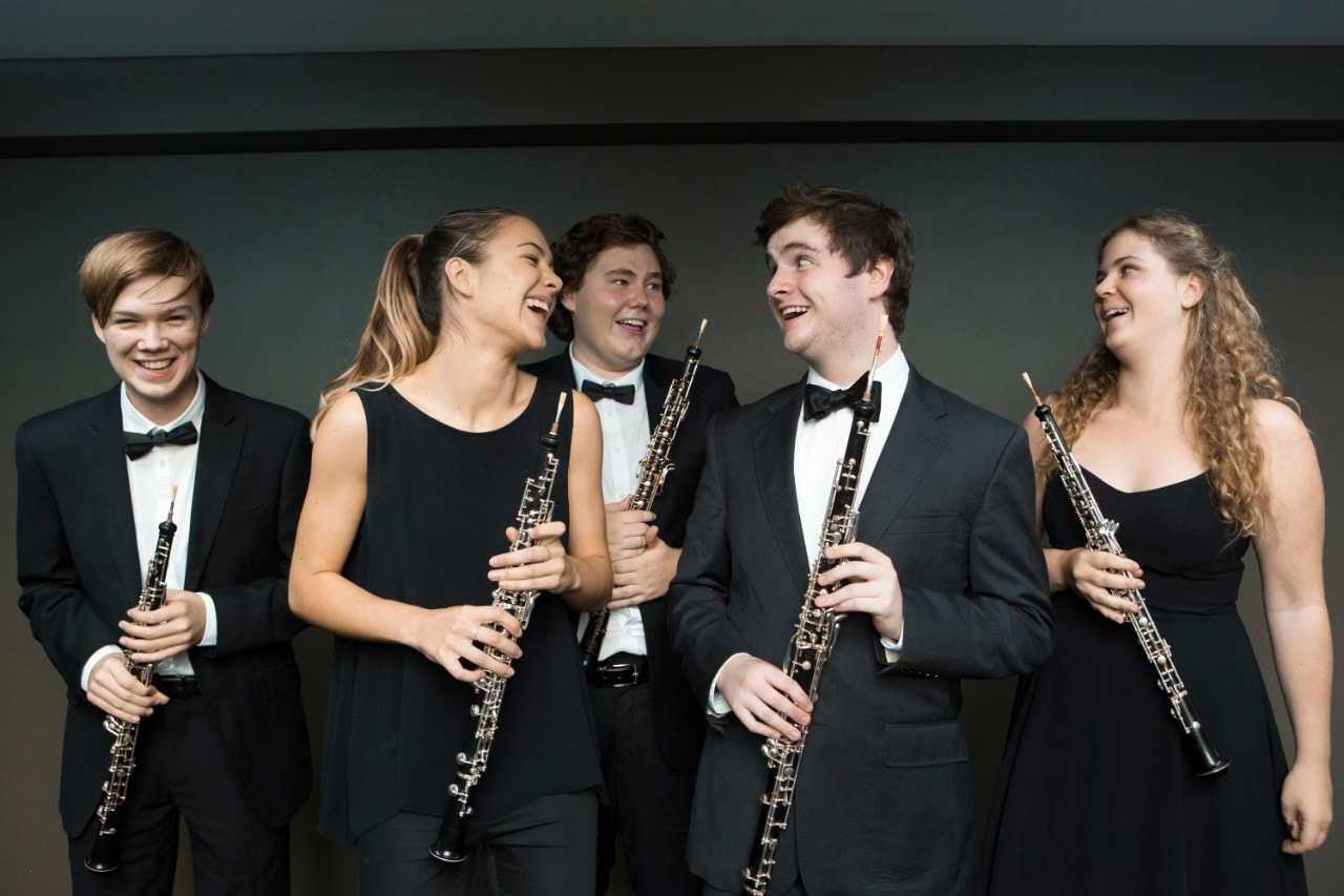 Photo of a group of musicians smiling and laughing
