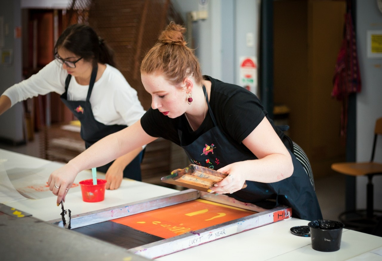 photo of a young student working on a screen print