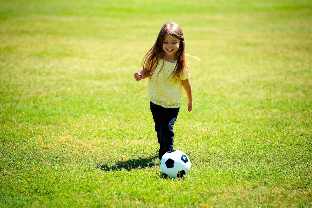 photo of a small girl kicking a soccer ball