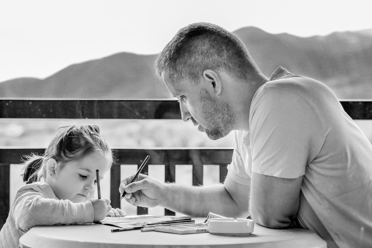 Photo of a father helping his daughter with her school work