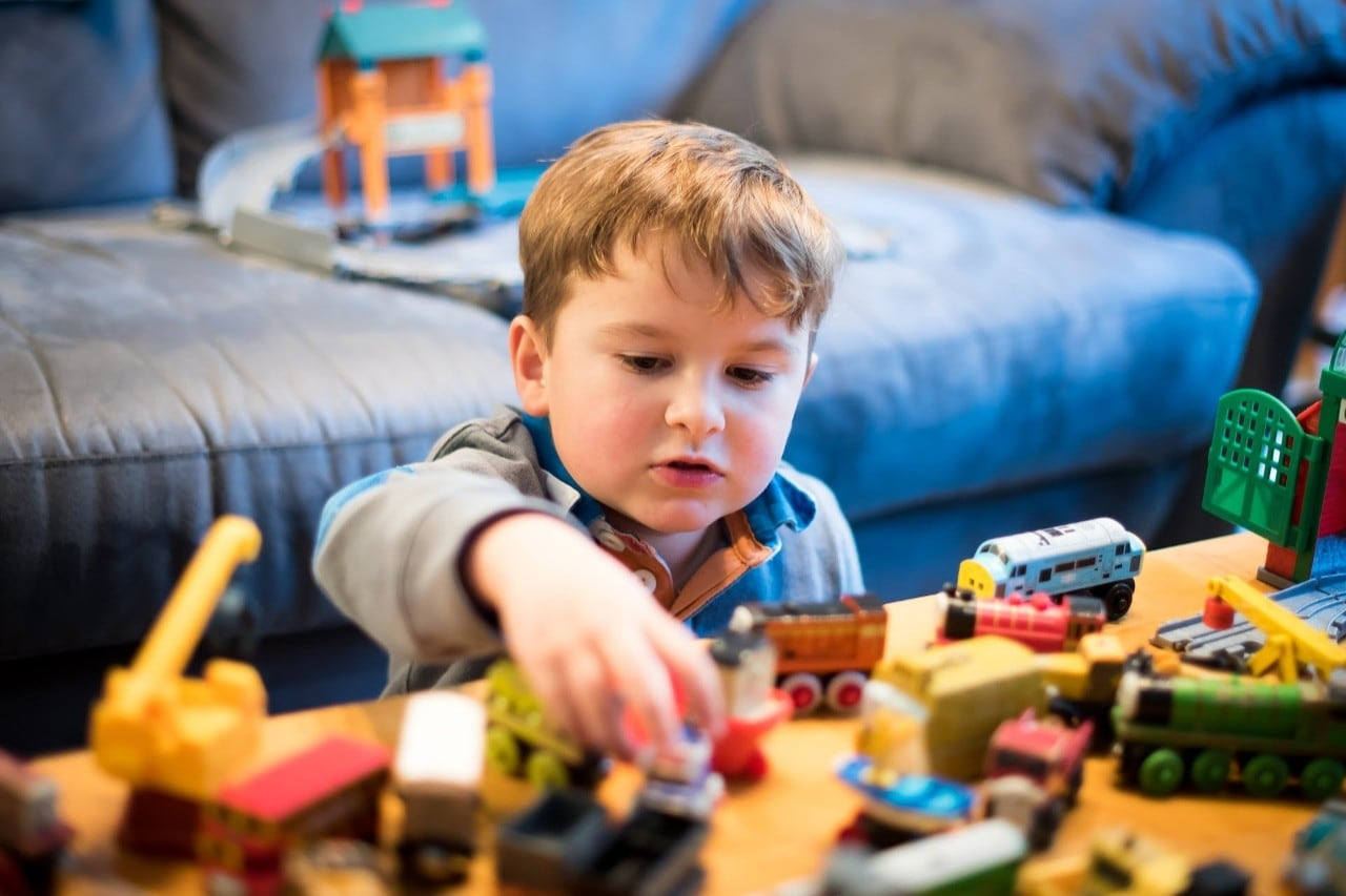 Photo of a boy playing with toy trains