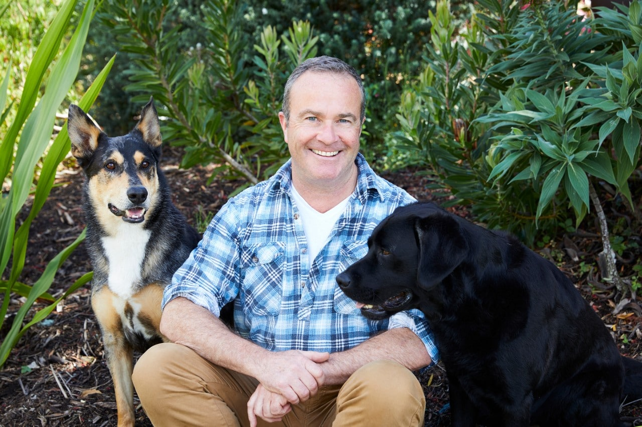 Photo of Professor Paul McGreevy patting his two dogs.