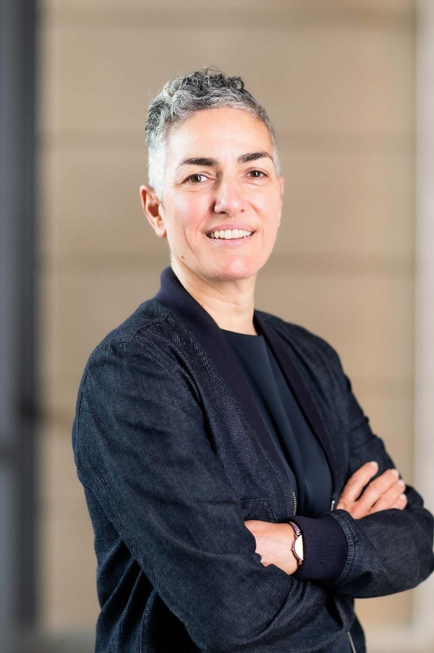 Professor Annamarie Jagose, in front of sandstone brick wall
