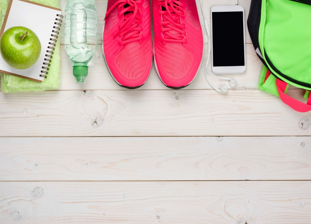 A green apple, a water bottle, running shoes and a phone lined up together