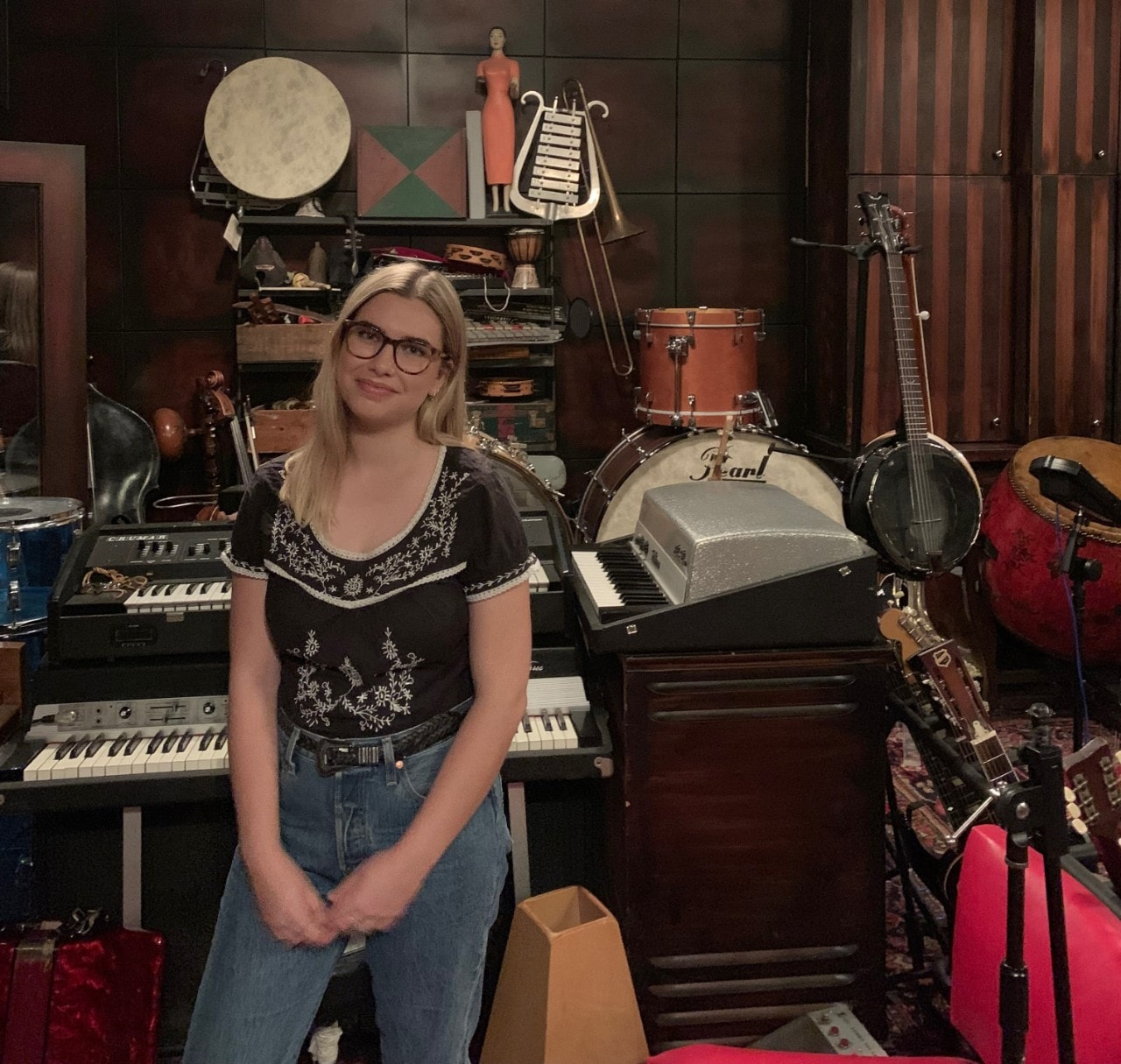 Chloe Sinclair in the Matter Music studio surrounded by musical instruments and memorabilia