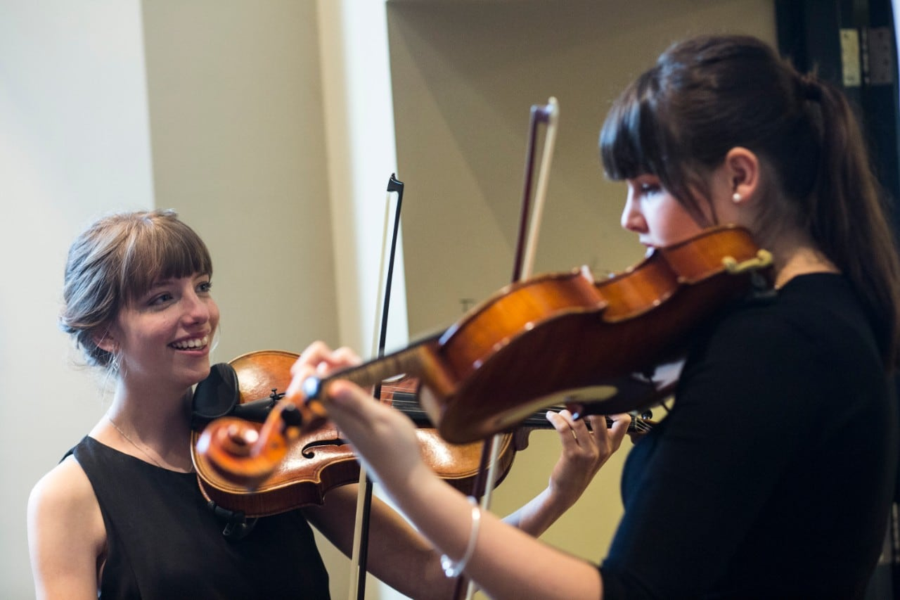 Two female violinists facing each other while playing music