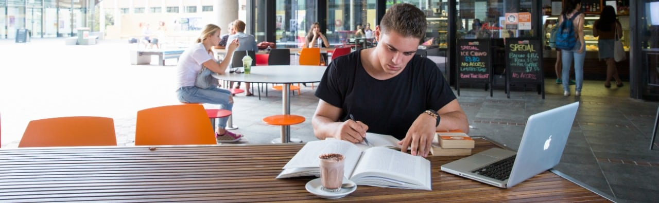 Student studies in a cafe setting