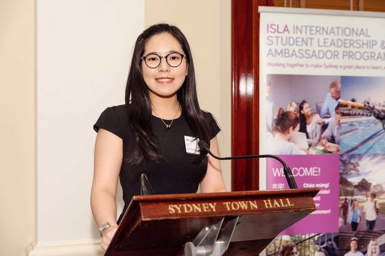 Anyi Li standing at a Sydney Town Hall lectern