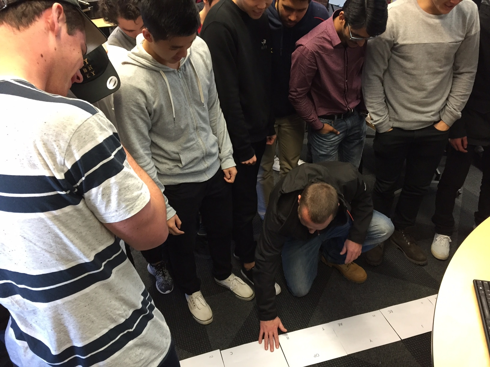 Above shows students attempting to solve the final riddle as a whole class after solving their respective group puzzles.