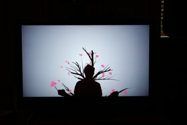 A person in silhouette form standing in front of an interactive and illuminated screen which features branches and pink flowers blooming from their silhouette.
