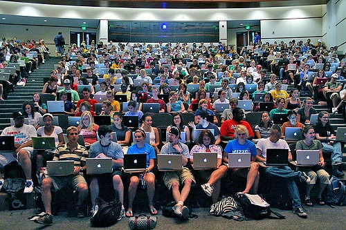View of a lecture theatre taken from the teacher's perspective, with all students with laptops. The lecture theatre is full and the majority of laptops feature the Apple logo.