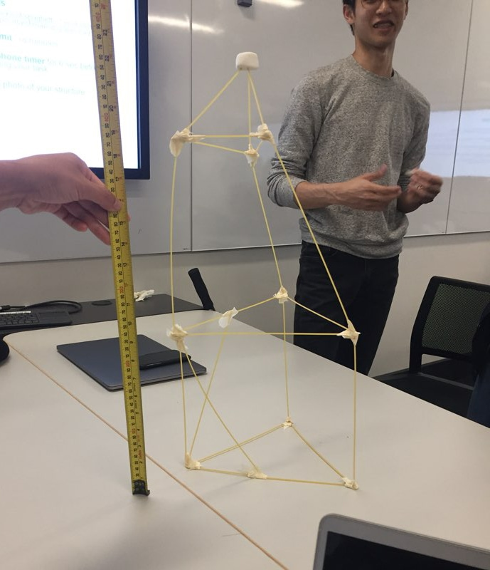 A student next to a marshmallow challenge structure that is being measured.