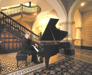 From the cover of 'Reflections on Mozart': Gerard Willems at the Stuart & Sons piano, Admiralty House.