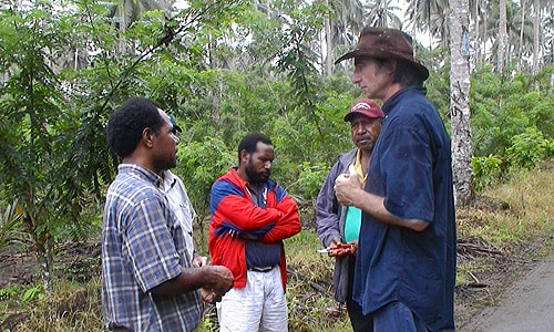 Professor David Guest (right) in Papua New Guinea with local scientists John Konam (left) and Anthon Kamuso (centre) with cacao farmers.
