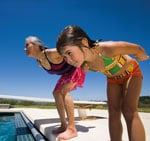 A young girl and older woman about to dive into pool