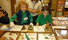 primary school children handling exhibits wearing gloves