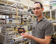 Dr Simon Lefrancois from the University of Sydney's School of Physics holding an optical chip used in the terabit oscilloscope