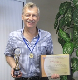 Professor Chris Dickman with his certificate, medal and statue from the Zoological Society of India