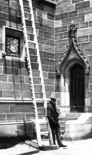 Chemistry professor John Smith leaning against a ladder near the Great Hall
