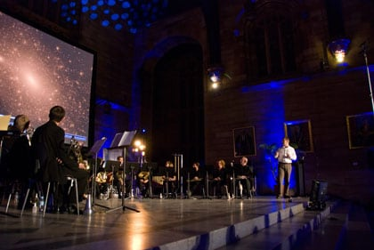 Professor Geraint Lewis explains galactic cannibalism, with the Sydney Conservatorium of Music Brass Ensemble on the stage in the Great Hall at Music and the Cosmos.